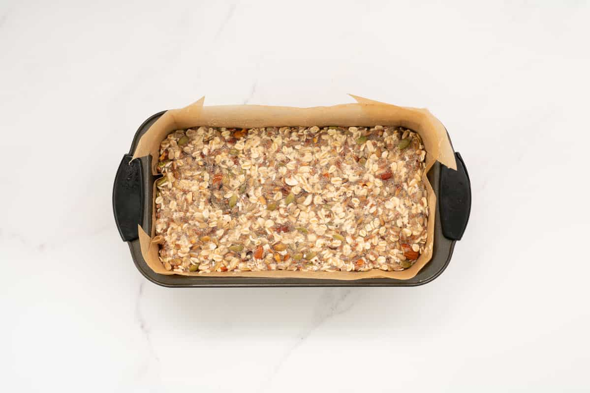 Oatmeal bread mix in a lined loaf tin.
