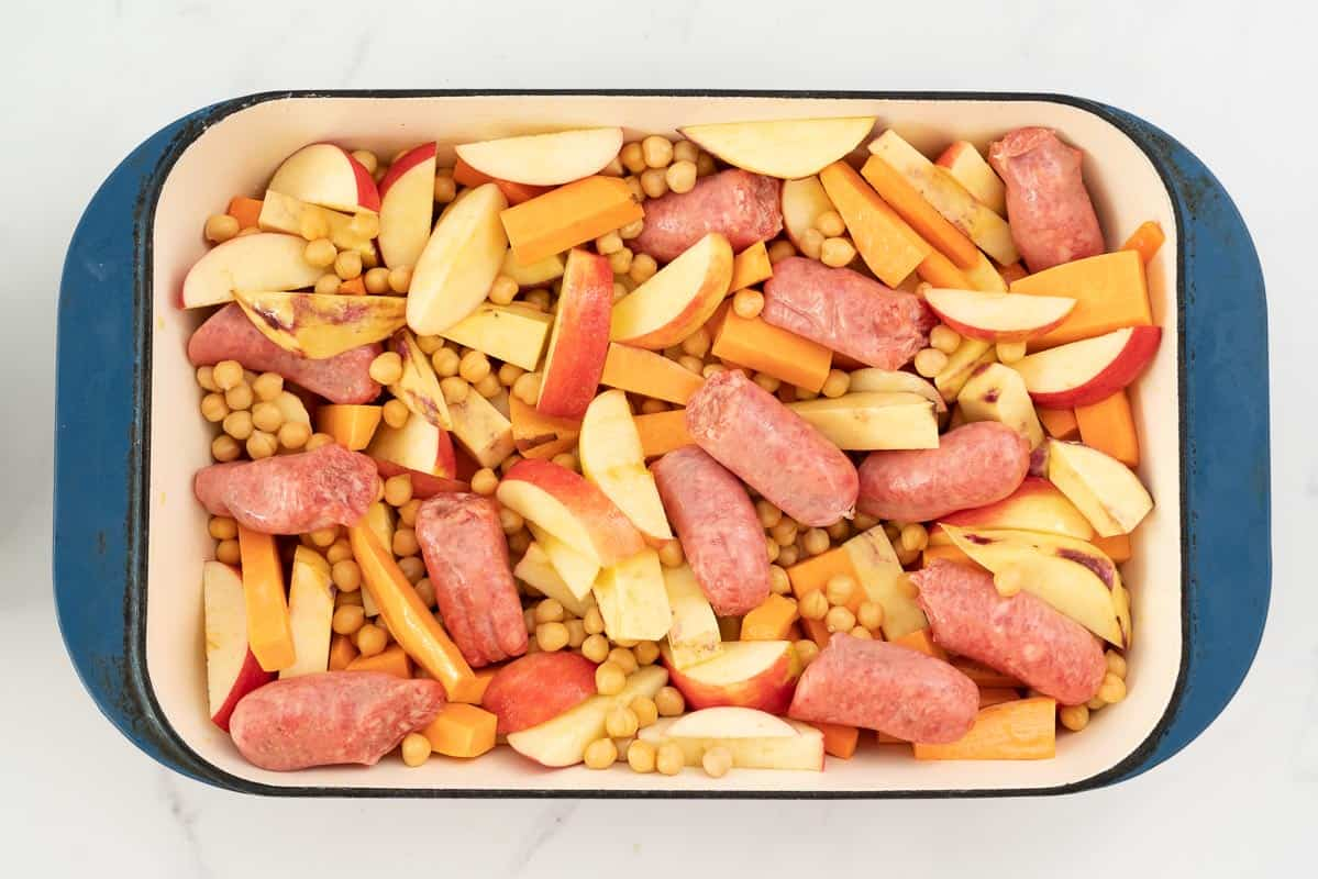 Sliced apples, carrots, sweet potato, sausages and chickpeas in a large blue ceramic roasting pan.