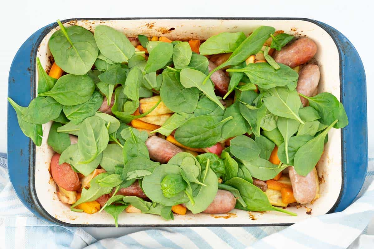 Spinach leaves on top of roasted vegetables and sausages in a blue ceramic roasting pan.