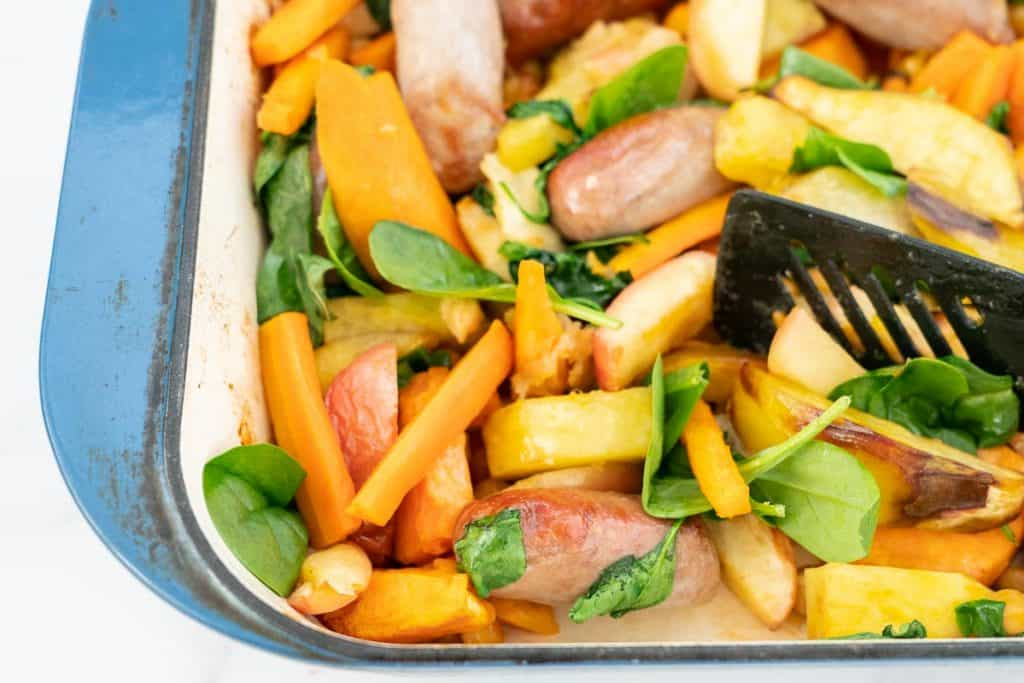 Close up of Baked sausages, apples, sweet potato and spinach leaves in a blue ceramic roasting pan.