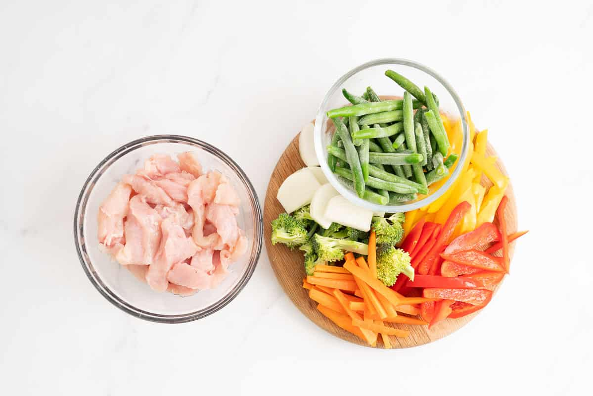 A medium glass bowl of sliced chicken breast and a wooden chopping board covered in sliced vegetables.
