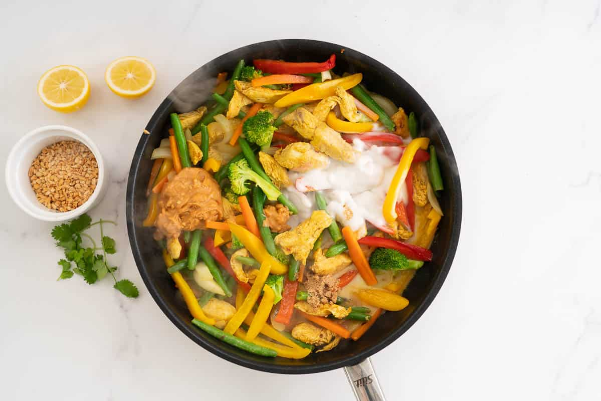 Stir fry vegetables and chicken with coconut cream and peanut butter visible in the pan.