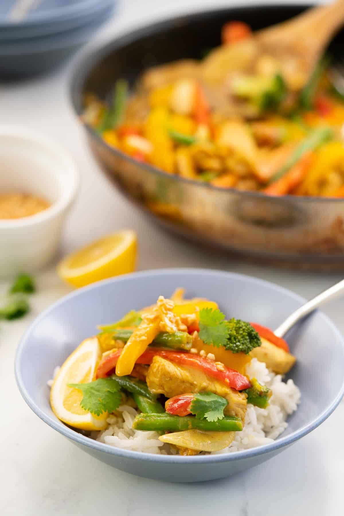 A bowl of chicken satay stir fry on a bed of rice, with a large fry pan in the background.