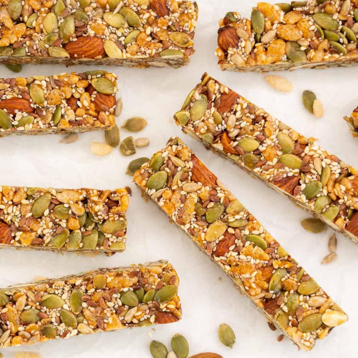 Energy bars on white crumpled baking paper surrounded by scattered nuts and seeds.