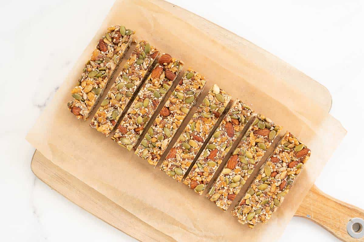Eight energy bars sitting on a piece of baking paper.