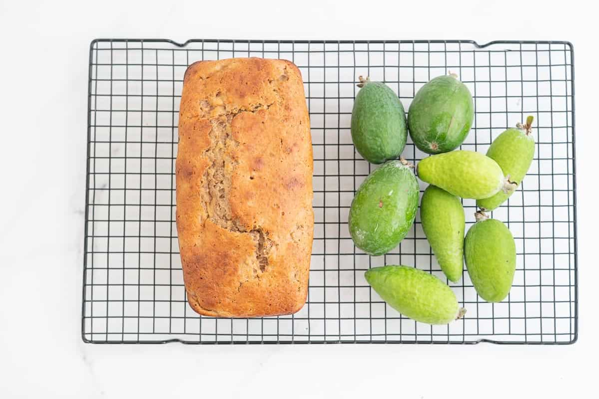 Golden brown loaf sitting on a cooling rack next to a pile of feijoas.