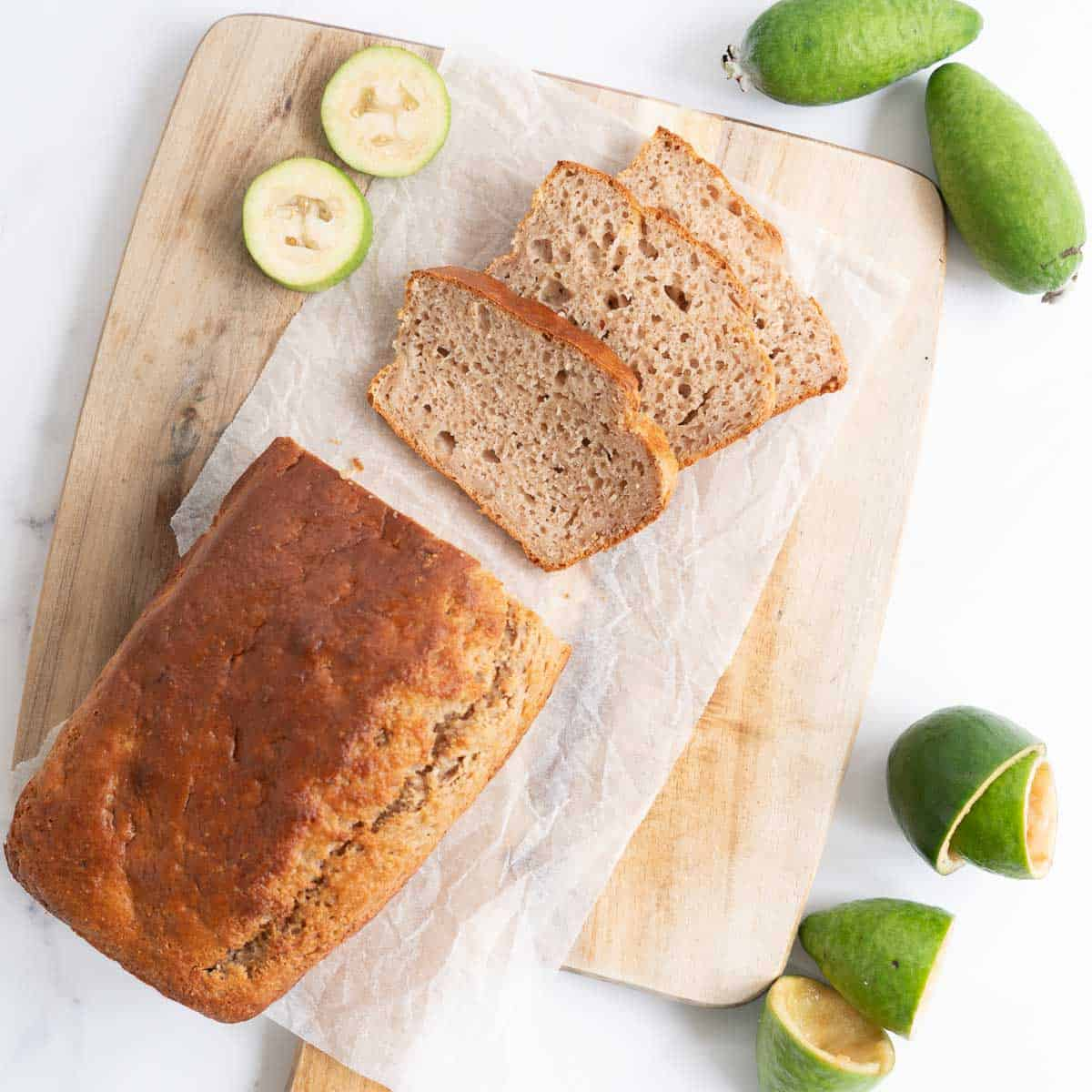 Feijoa loaf on a chopping board, three slices cut from the loaf.