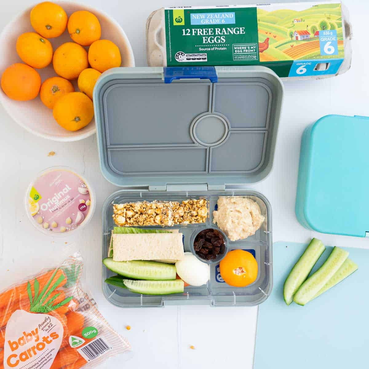 A child's bento style lunchbox packed with an assortment of food including popcorn bars.