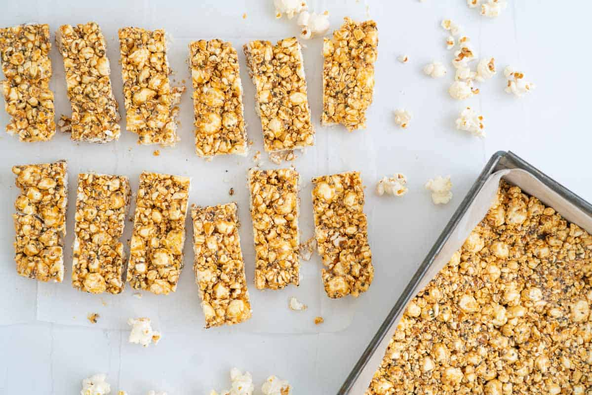 Popcorn bars on a bench top scattered with loose popcorn kernels.