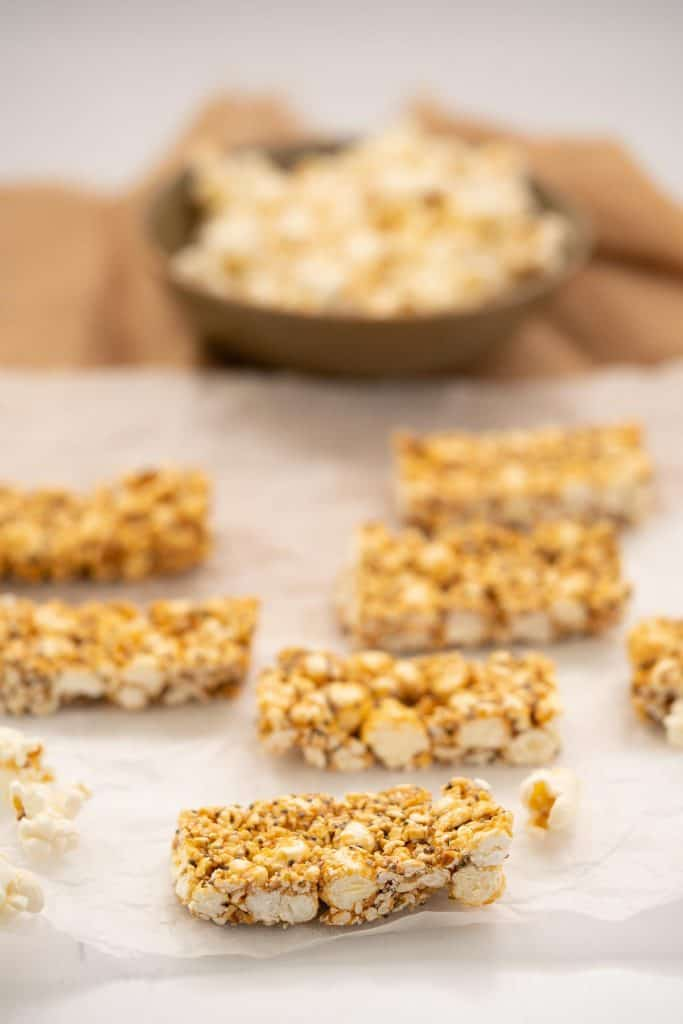 Popcorn bars sitting on a piece of baking paper, bowl of popcorn in the background.