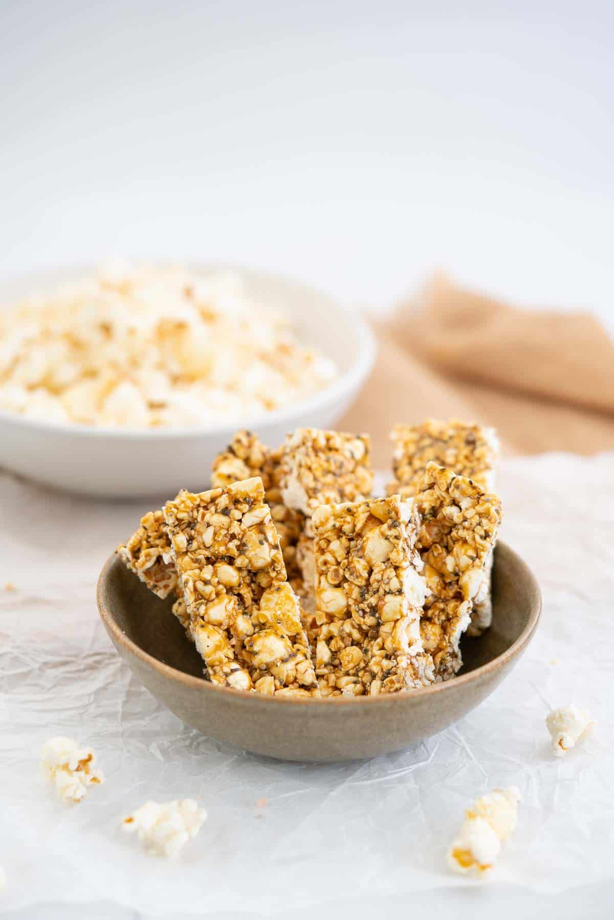 Brown ceramic bowl filled with 6 popcorn bars, a bowl of popcorn in the background.