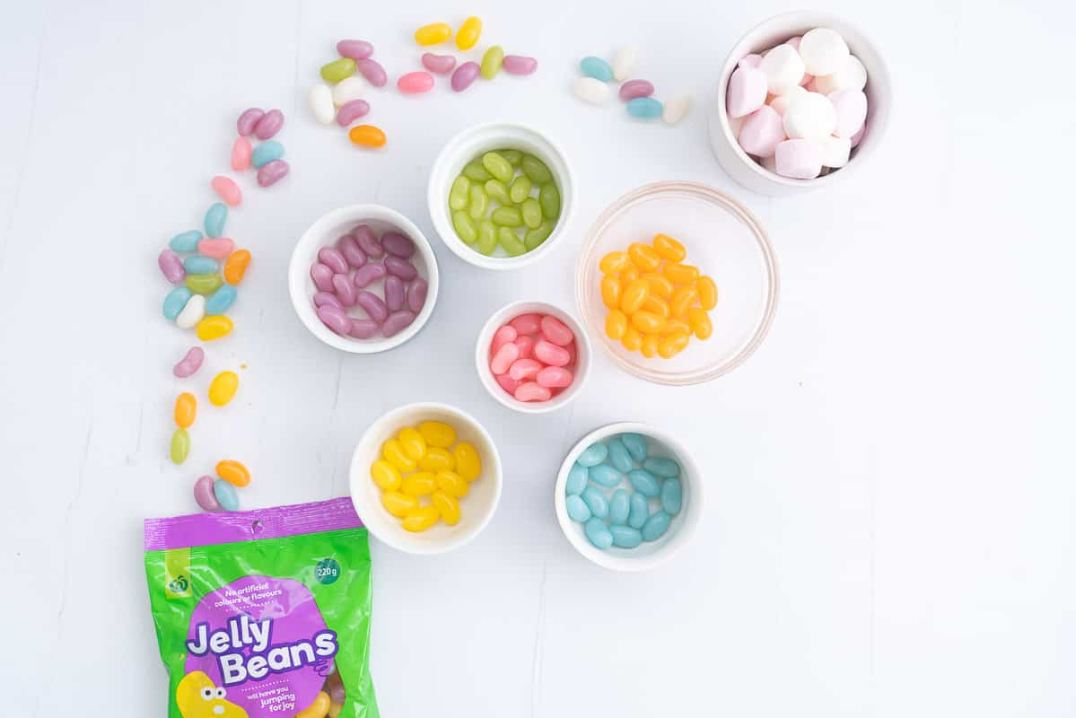 Jelly beans sorted into six small bowls by colour.