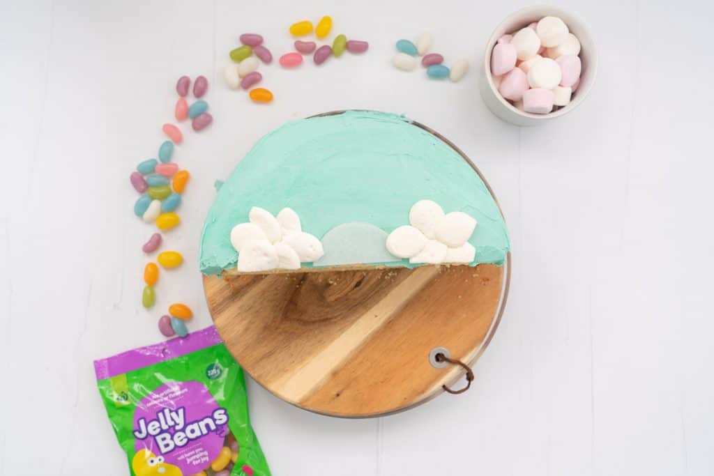 A half round cake, iced in blue, with 2 marshmallow clouds.