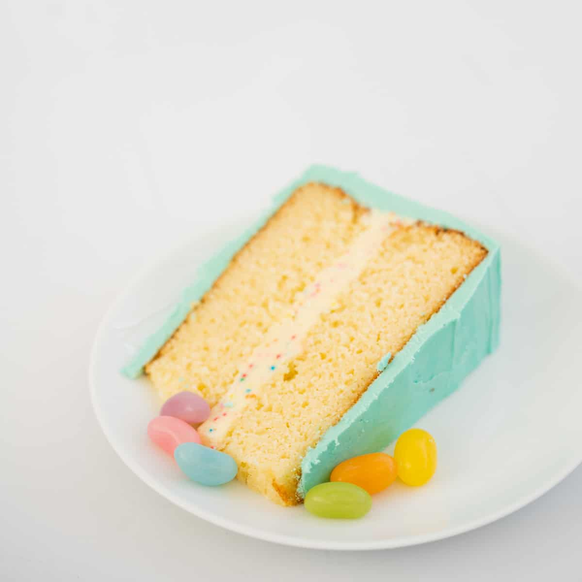 A slice of rainbow cake ready to serve on a white plate.