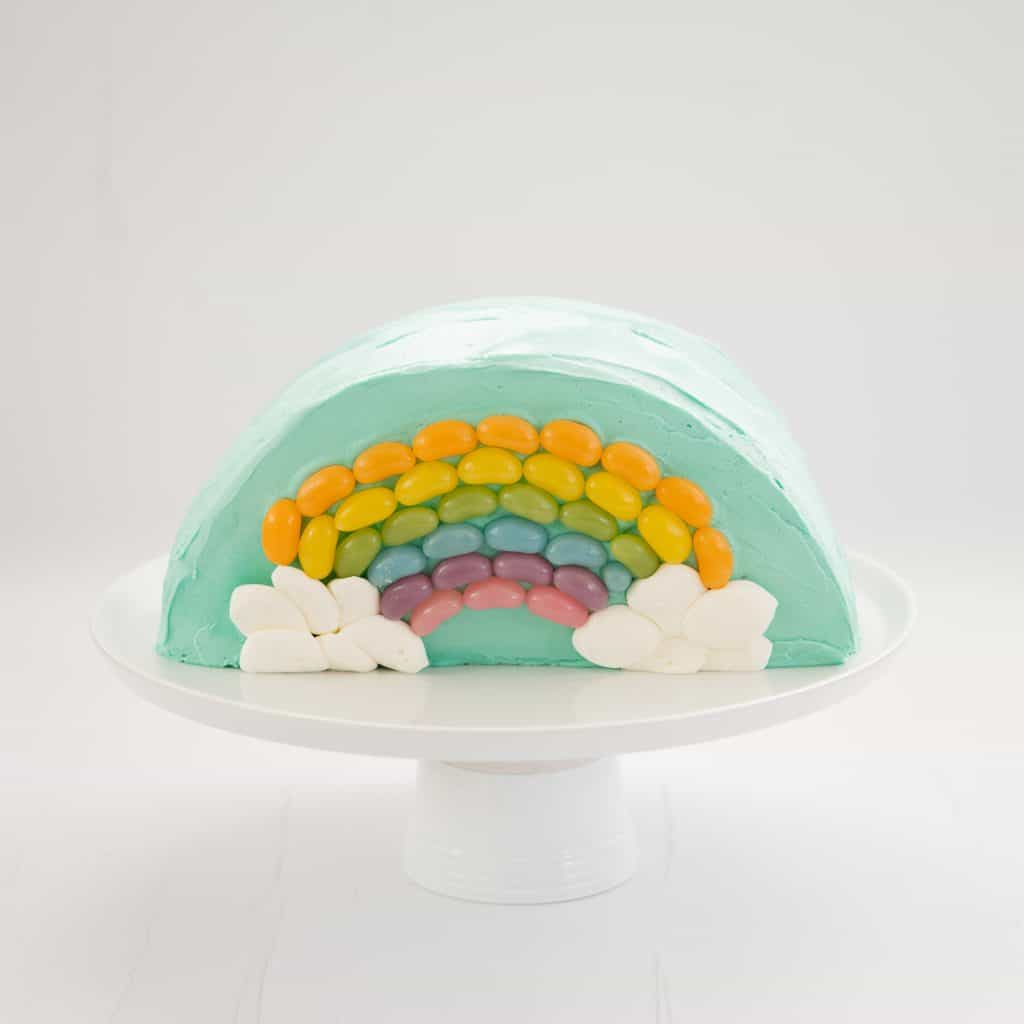 Rainbow Cake: Half round cake standing on a white serving platter decorated with a rainbow of jellybeans.