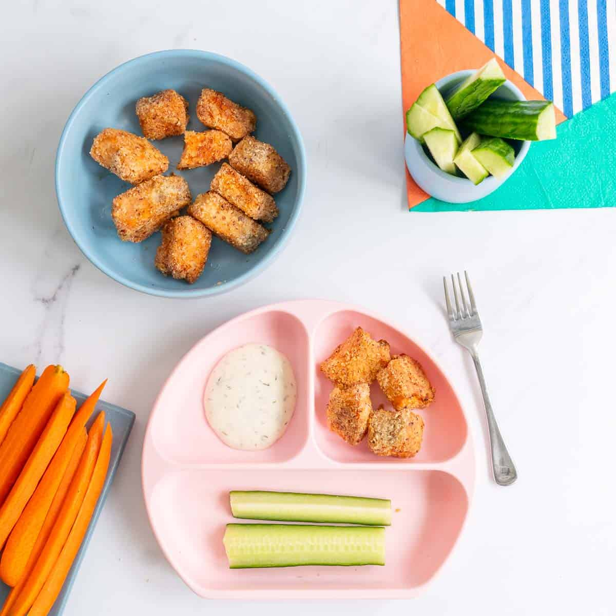 Baby meal served in a pink divided plate with salmon nuggets, cucumber and dipping sauce.
