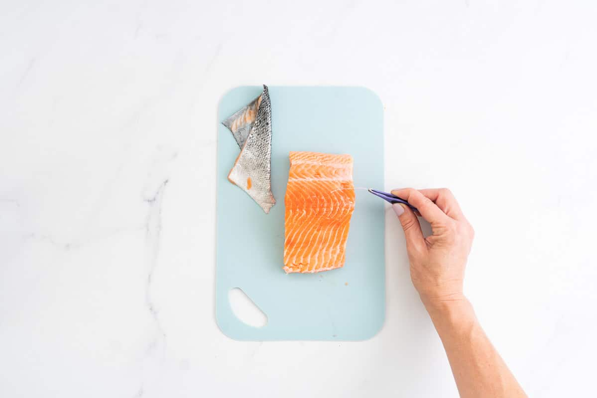 A salmon fillet with skin removed, hand using tweezers to remove bones.