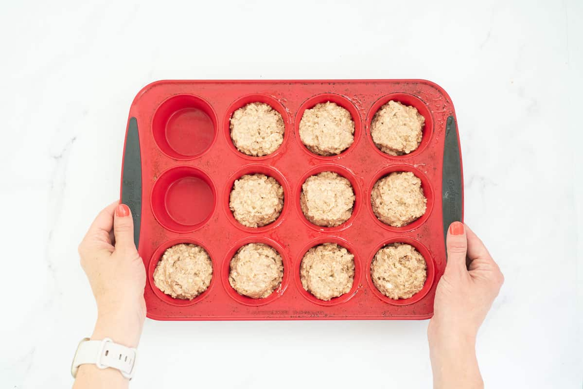 Muffin batter portioned into 10 of 12 cups in a red silicone muffin pan.