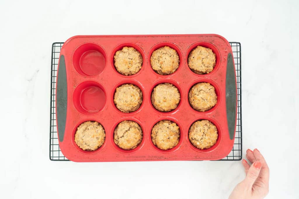 Apple toddler muffins baked to a golden colour in a red silicone muffin tray.
