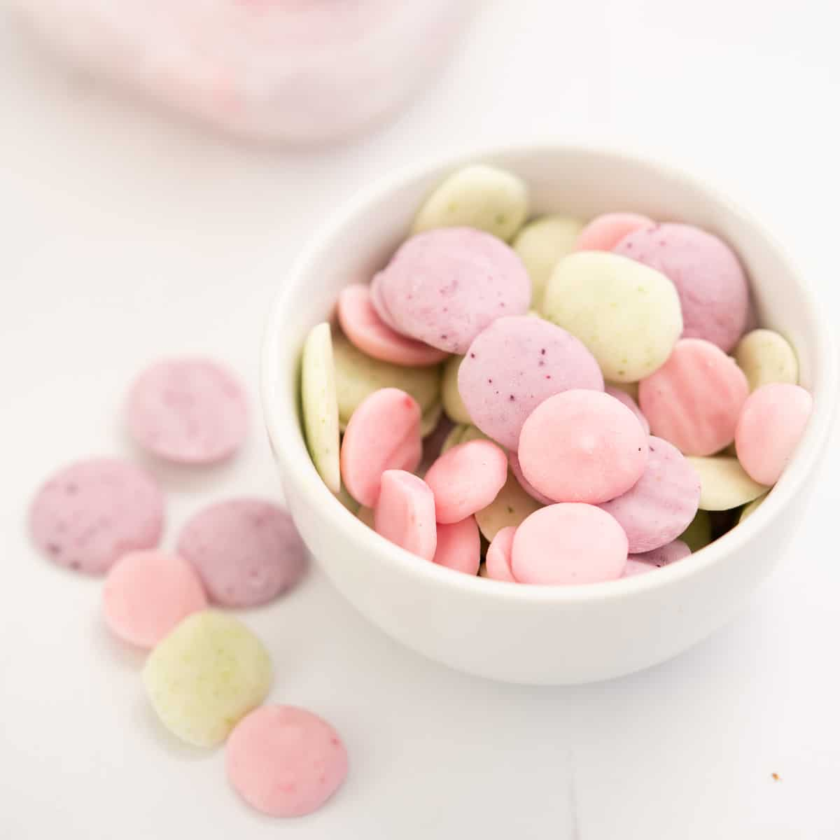 a small white bowl of baby yogurt melts in 3 colours, pale pink, lavender and pale green.