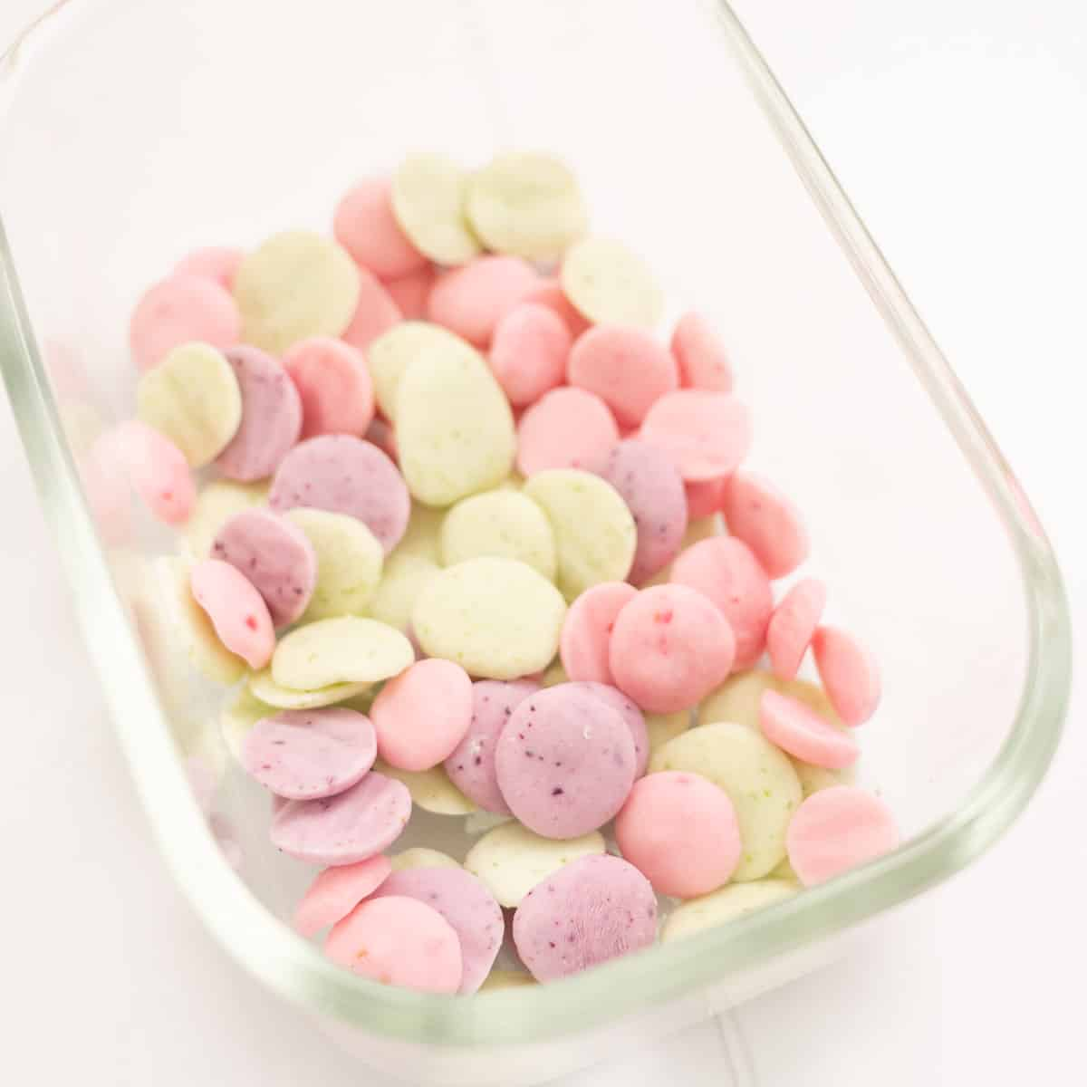 Three flavours (green, purple, pink) of baby yoghurt melts in a glass freezer container.