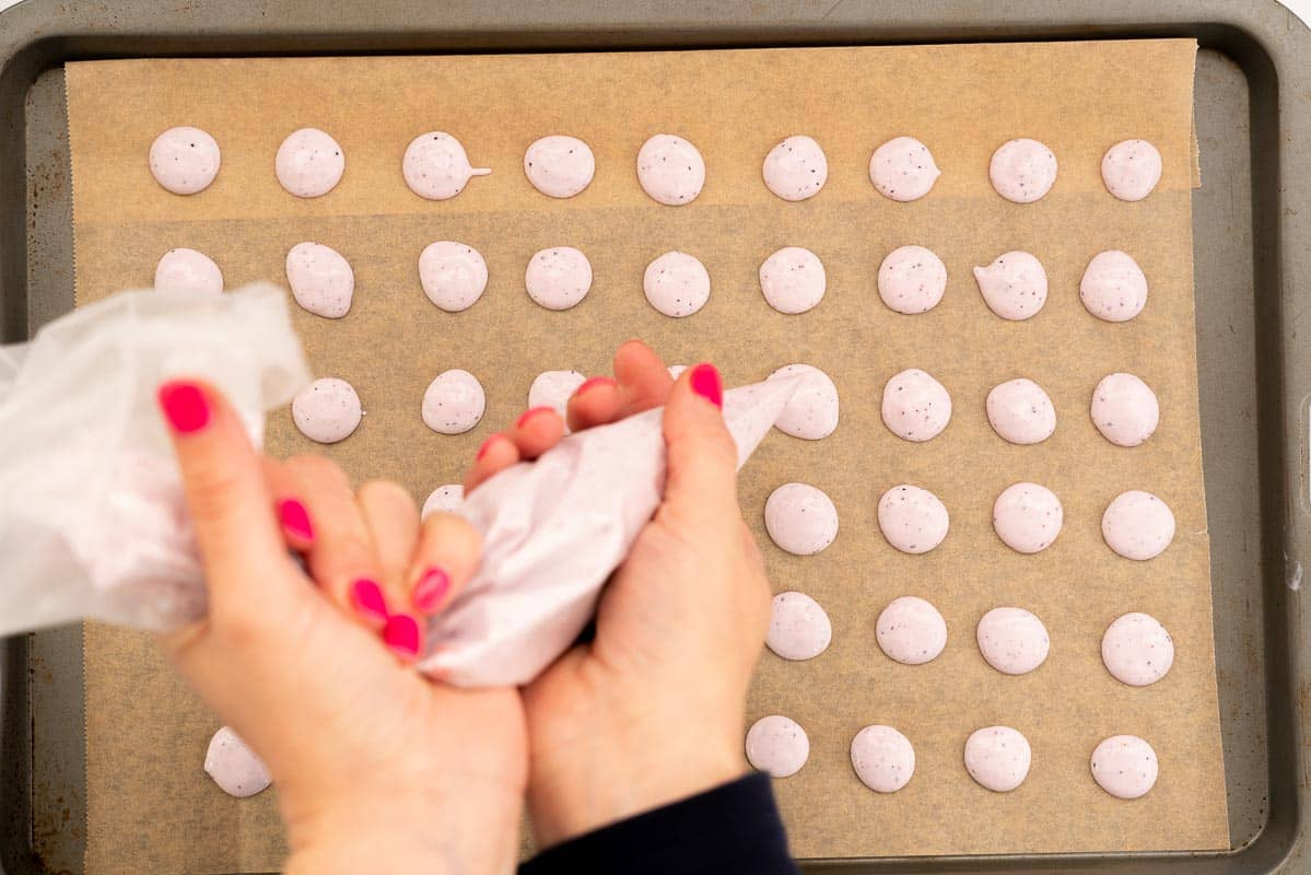Women's hands piping small buttons of flavoured yoghurt on to a baking paper lined tray.