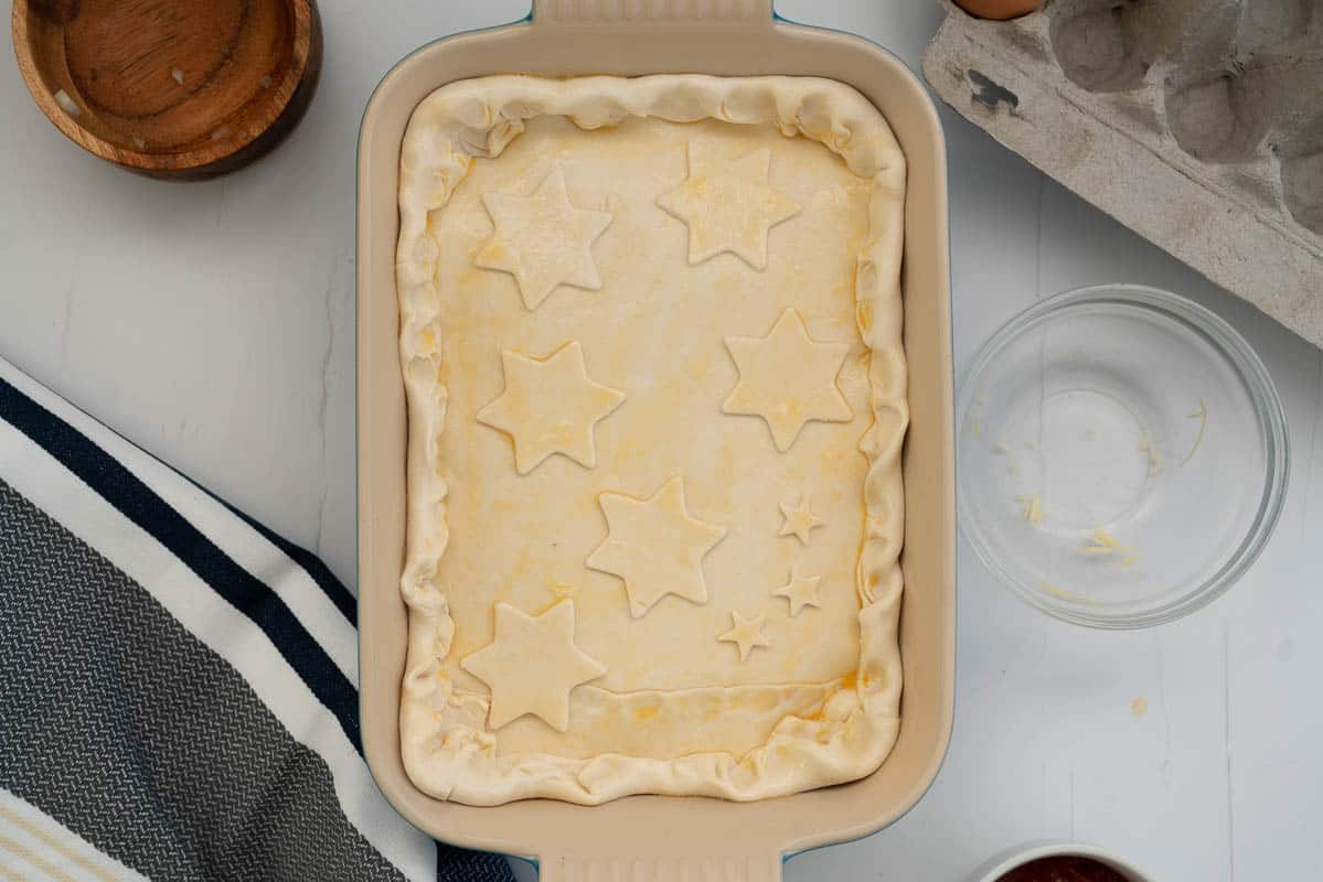Uncooked pie crust decorated with stars and brushed with an egg wash.