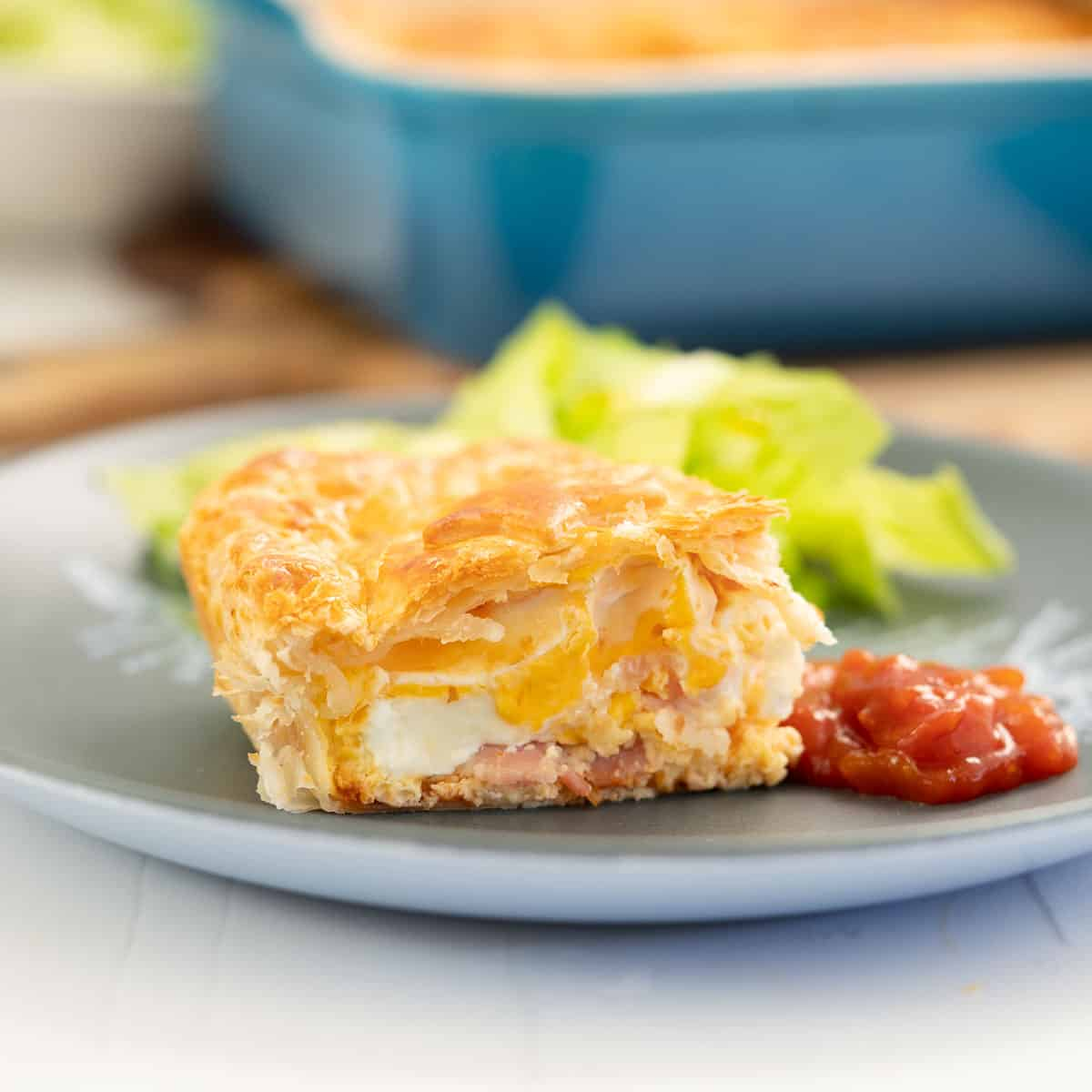 A slice of bacon and egg pie on a blue plate, with tomato relish and salad.