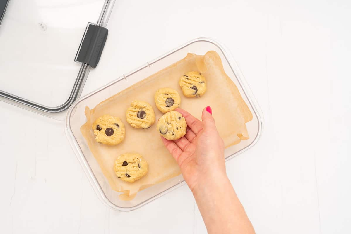 Cookie dough balls being placed in a baking paper lined container ready to freeze.