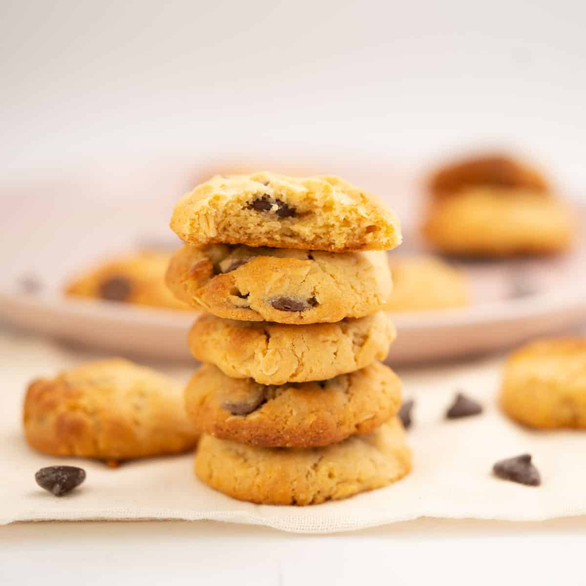 A stack of 5 condensed milk cookies in front of a plat of more cookies.