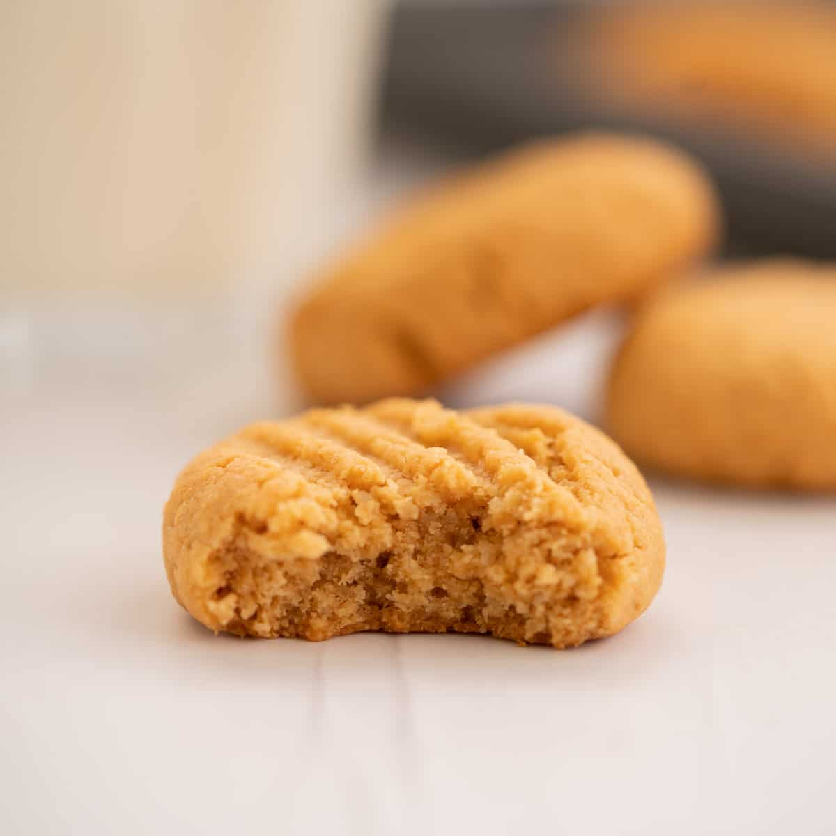 A peanut butter cookie that has been bitten in half revealing the soft cookie centre.