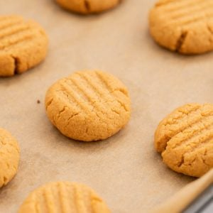 Baked cookies ready to come out of the oven on a baking paper lined tray.