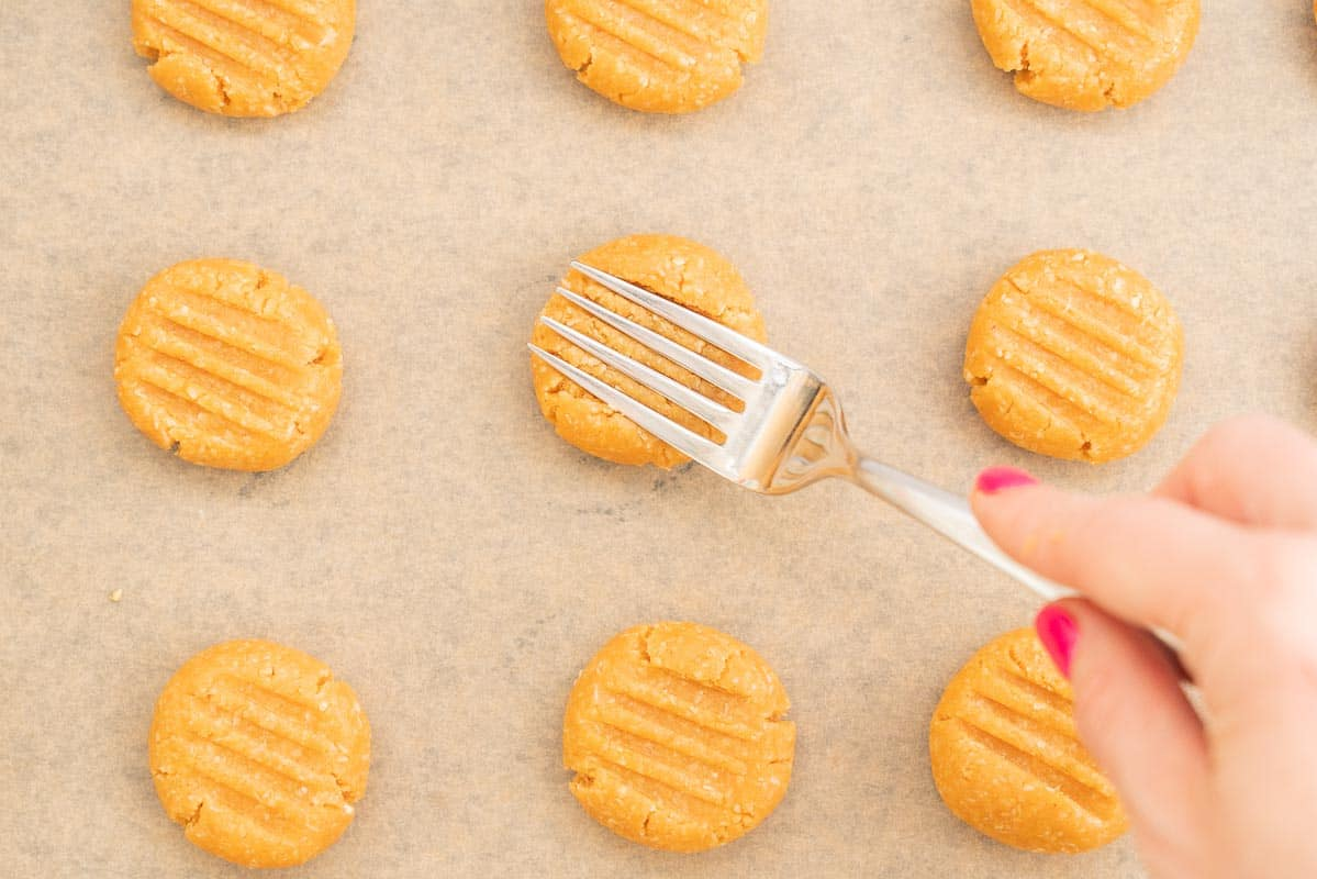 Women's hand pressing cookie dough balls with a fork.