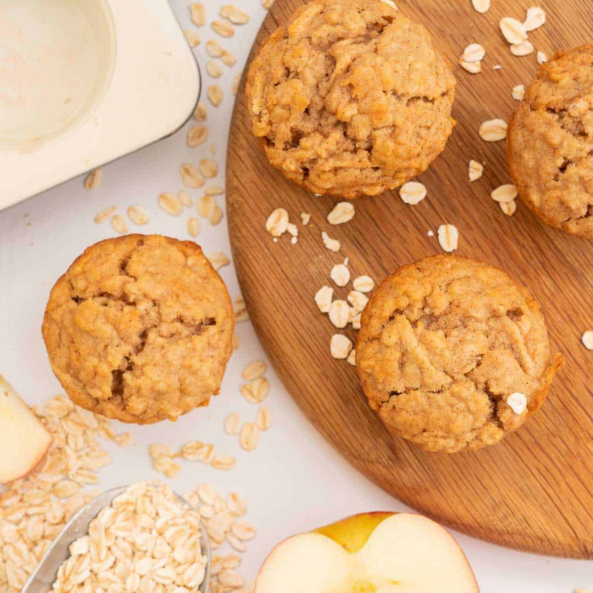 Over head shot of apple muffins on a wooden chopping board scattered with rolled oats.