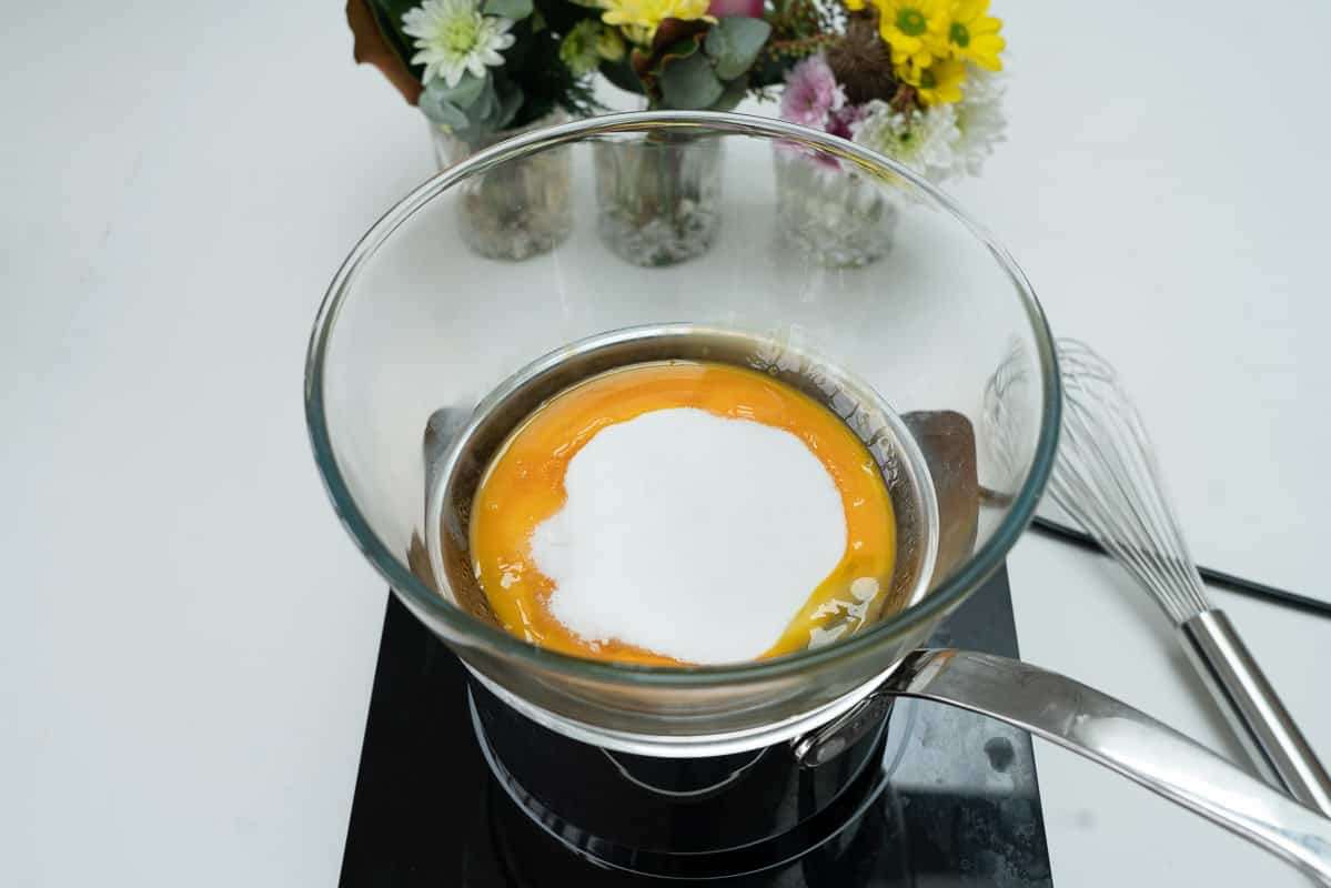 Egg yolks and sugar in a glass bowl sitting on top of a saucepan.