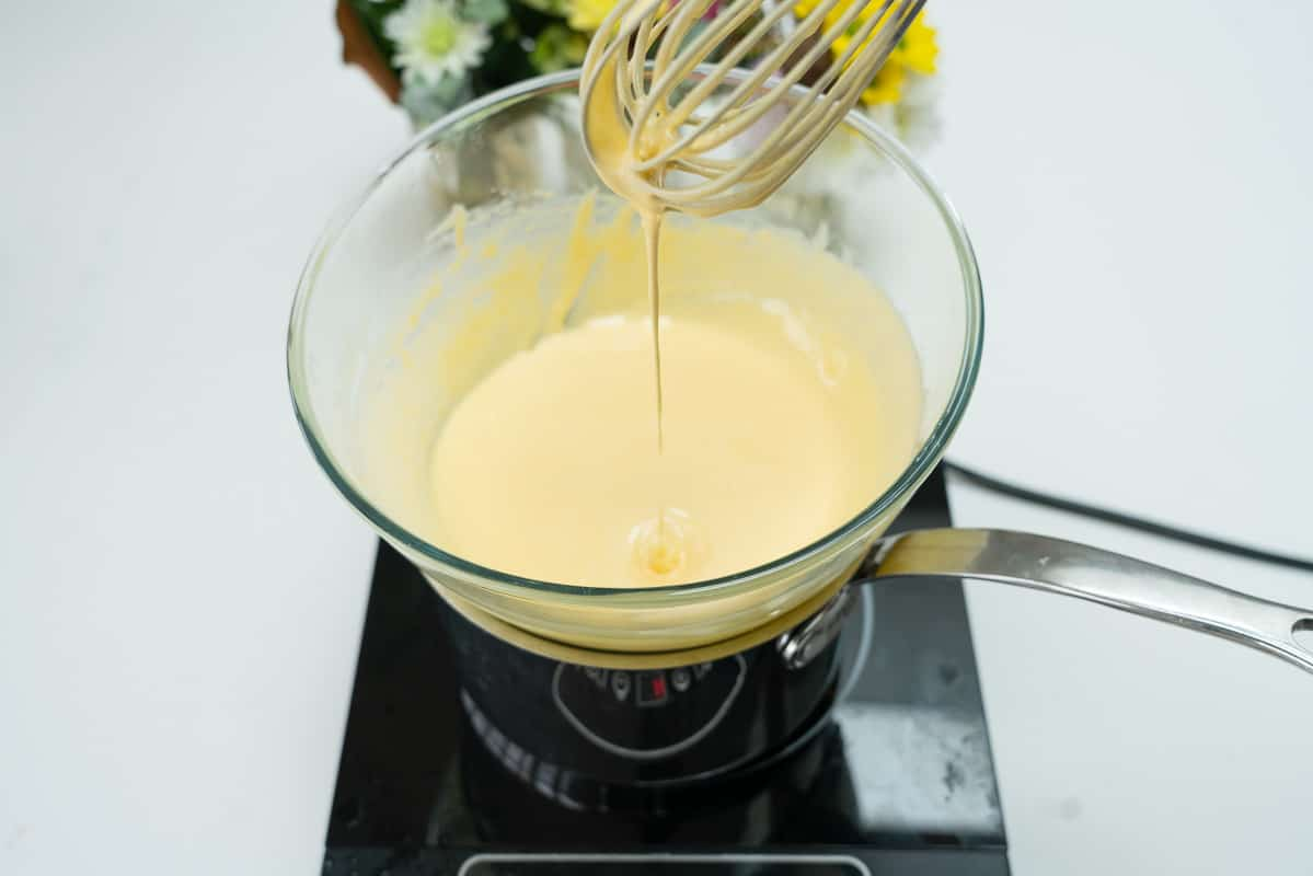 Custard in a glass bowl on top of a double boiler. Pale, and thickened,