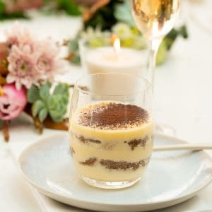 Tiramisu served in a glass, a candle, and flowers in the background.