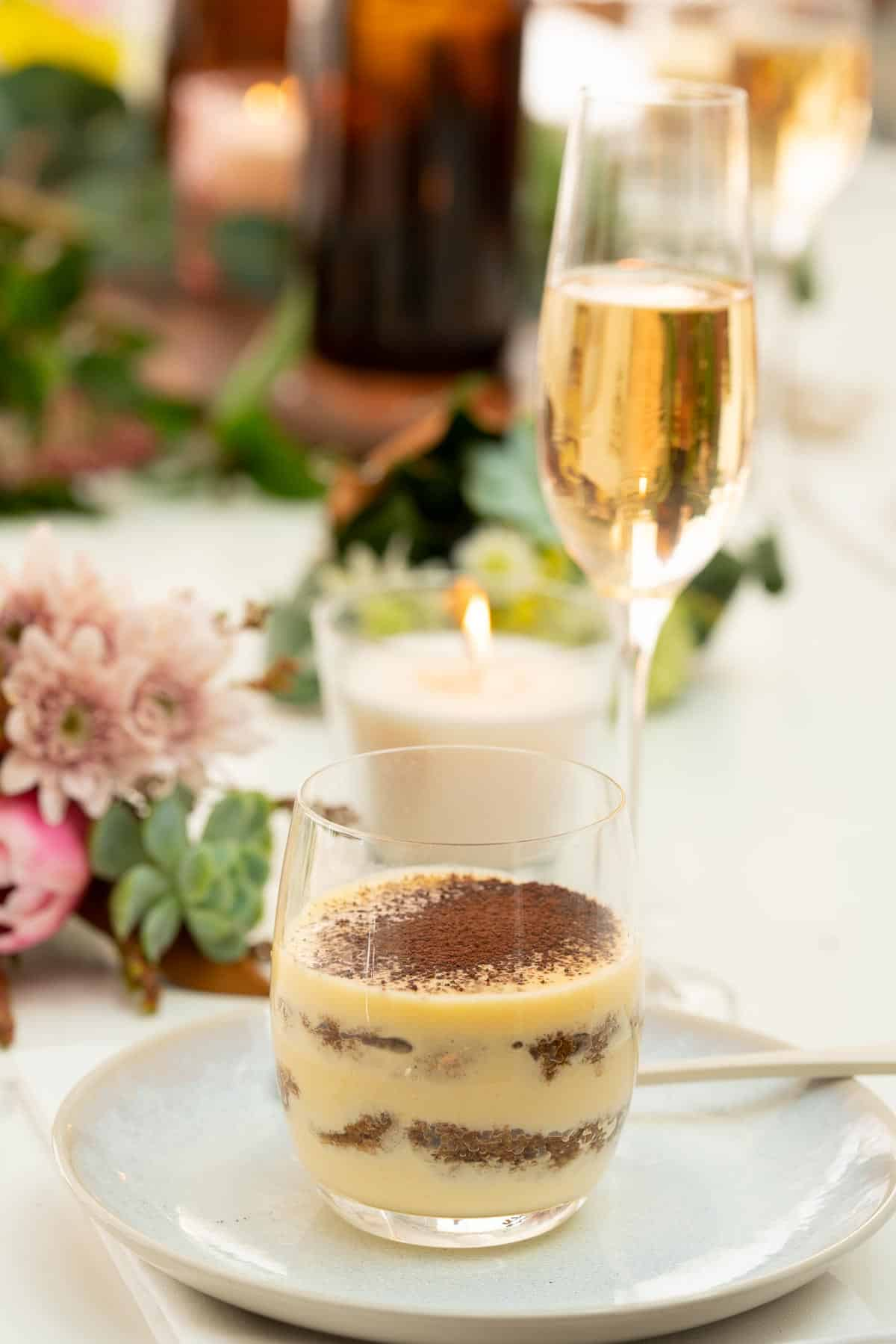 A tiramisu cup sitting on a table decorated with candles and fresh flowers, a glass of champagne and water dcanters visible in the background.