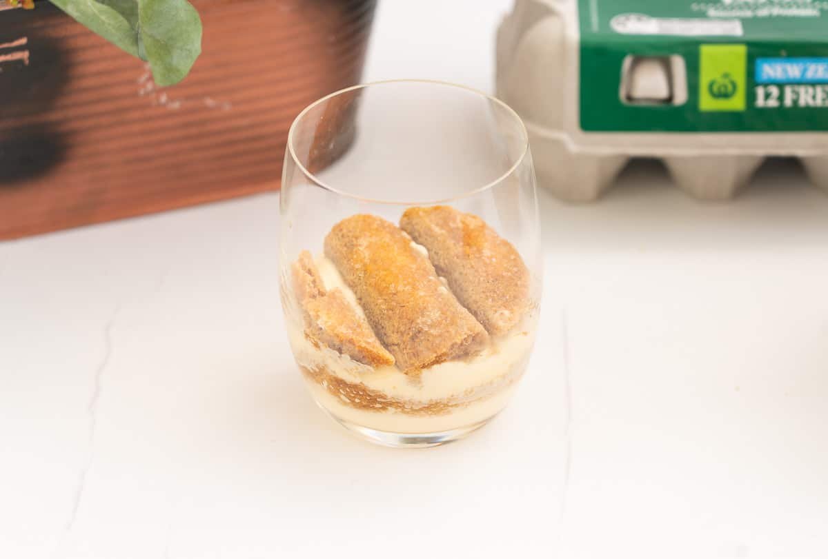 Layers of mascarpone cream and coffee soaked savoiardi biscuits in a glass.