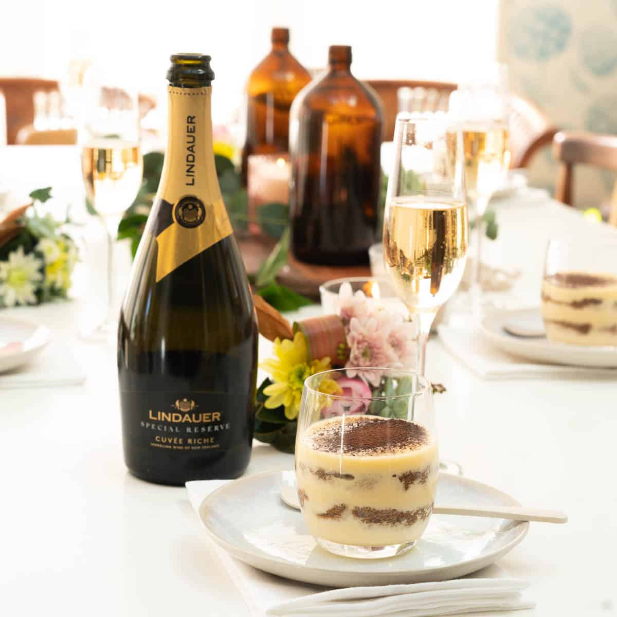 Tiramisu served in a glass, on a table set for a dinner party, a bottle of sparkling wine in the background.