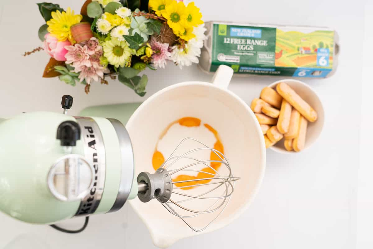Pale green stand mixer set up with whisk attachment, egg yolks and sugar in the mixing bowl.