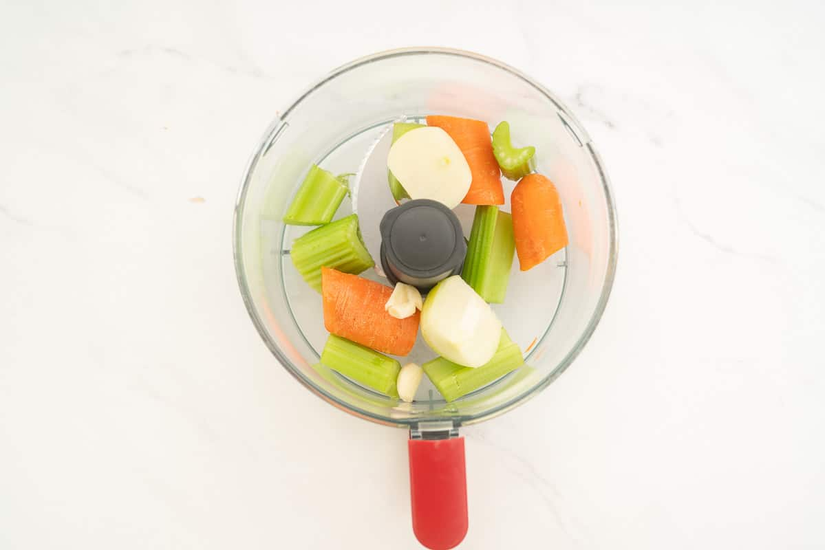 Roughly chopped onion, garlic, celery and carrot in a food processor.