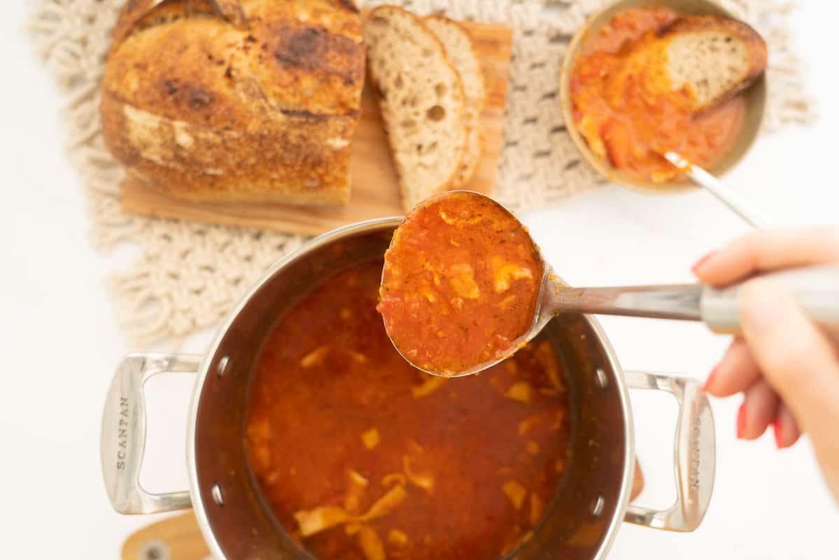 Tomato soup being ladled from a large saucepan into a bowl with crusty bread.