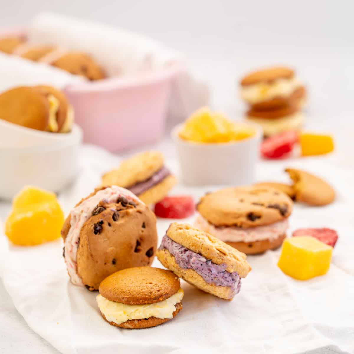 3 diffferent flavoured ice cream cookie sandwiches with frozen fruit pieces.
