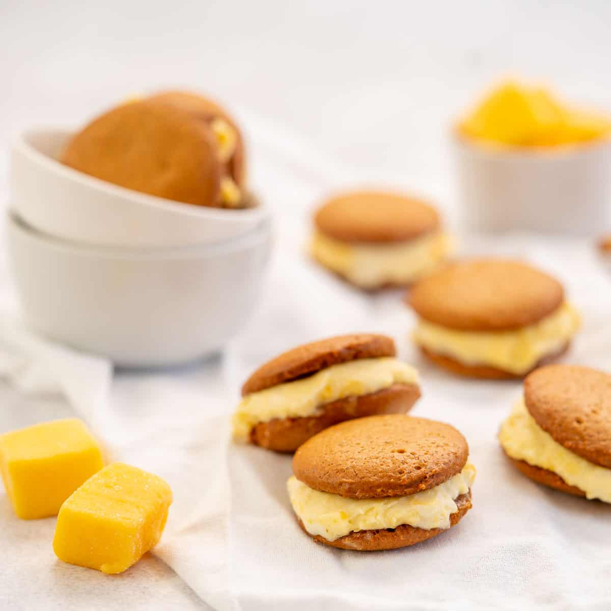Ginger biscuits sandwiched together with mango ice cream, sittin on a crinkled white linen napkin.