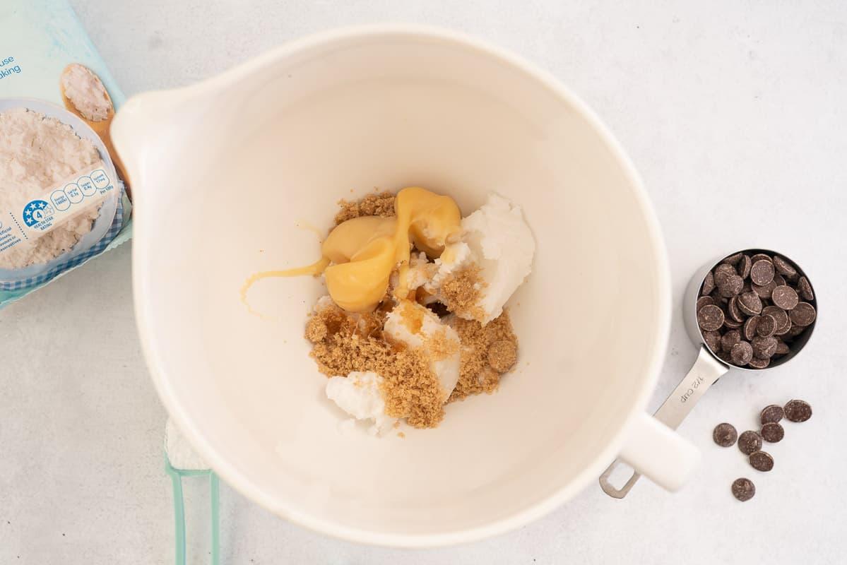 White ceramic mixing jug with coconut condensed milk, coconut oil and brown sugar.