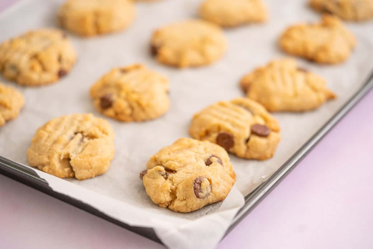 Golden baked chocolate chip cookies on a baking paper lined cookie sheet.