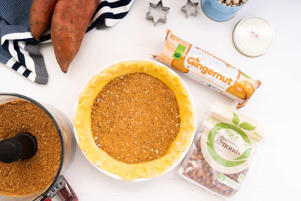 Pastry case in a pie dish with a layer of gingernut biscuit crumb pressed in the base.