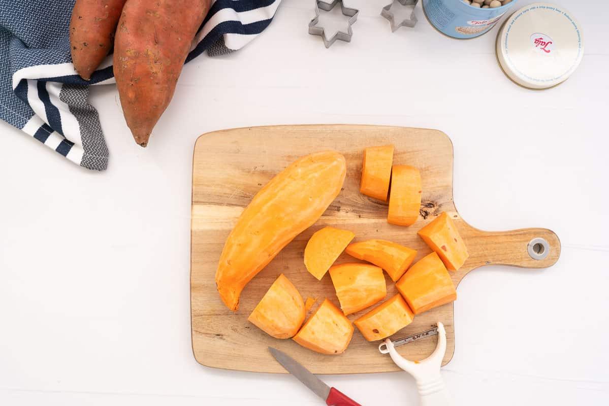 Peeled sweet potato on a wooden chopping board.
