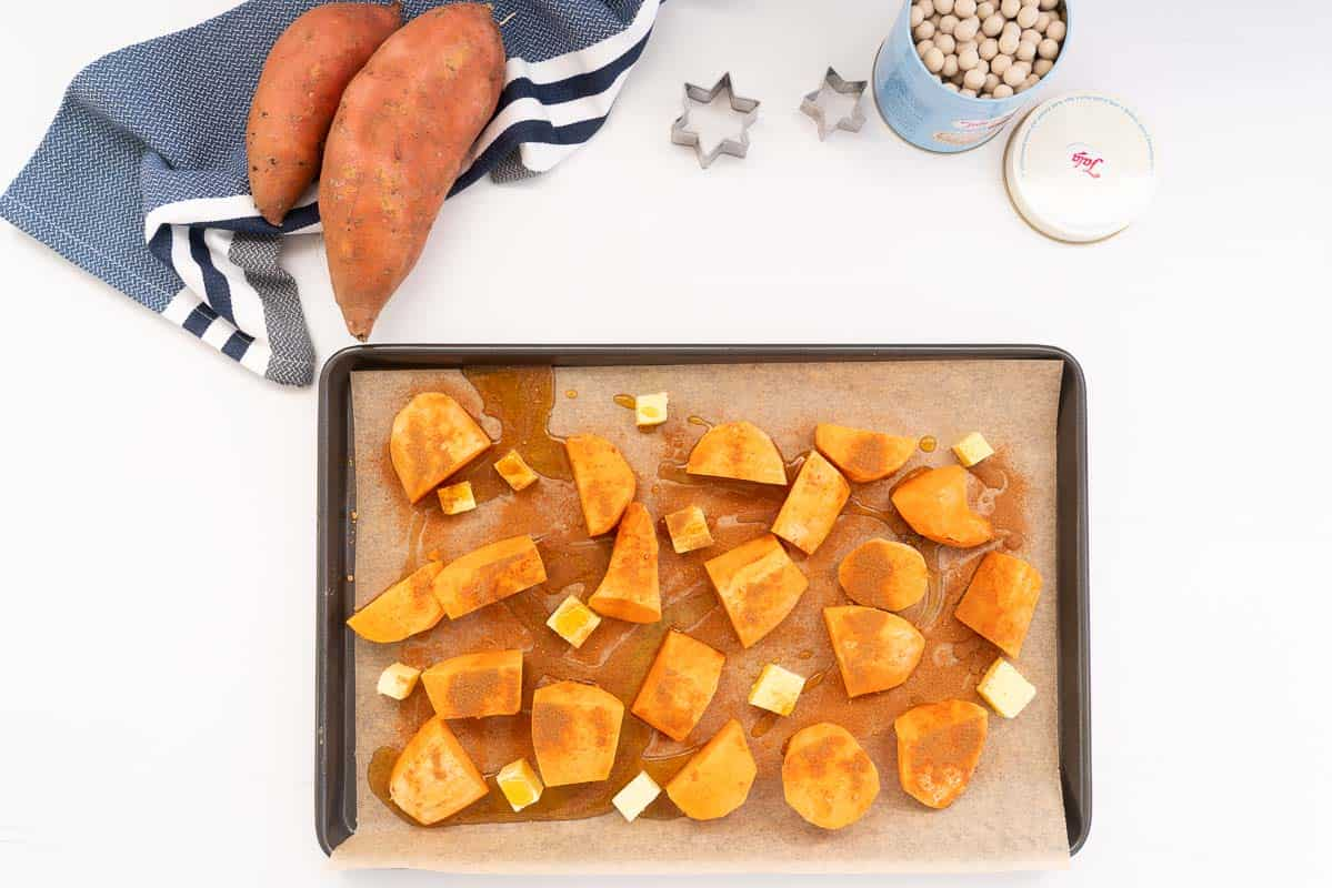 Pieces of sweet potato on a lined tray dusted with spices, and drizzled with maple syrup.